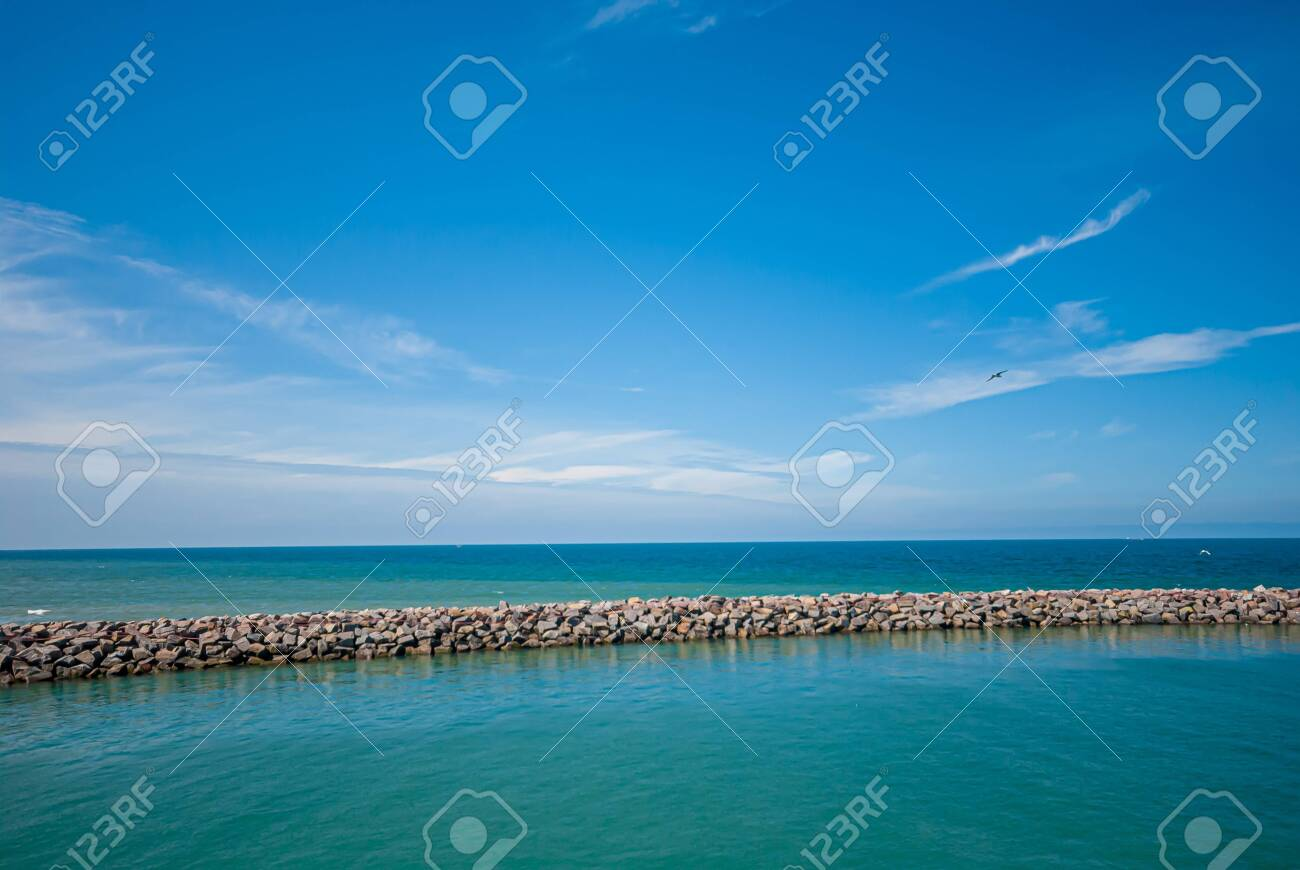 Breakwater with calm waters on the inside and rougher seas outside. - 132316110