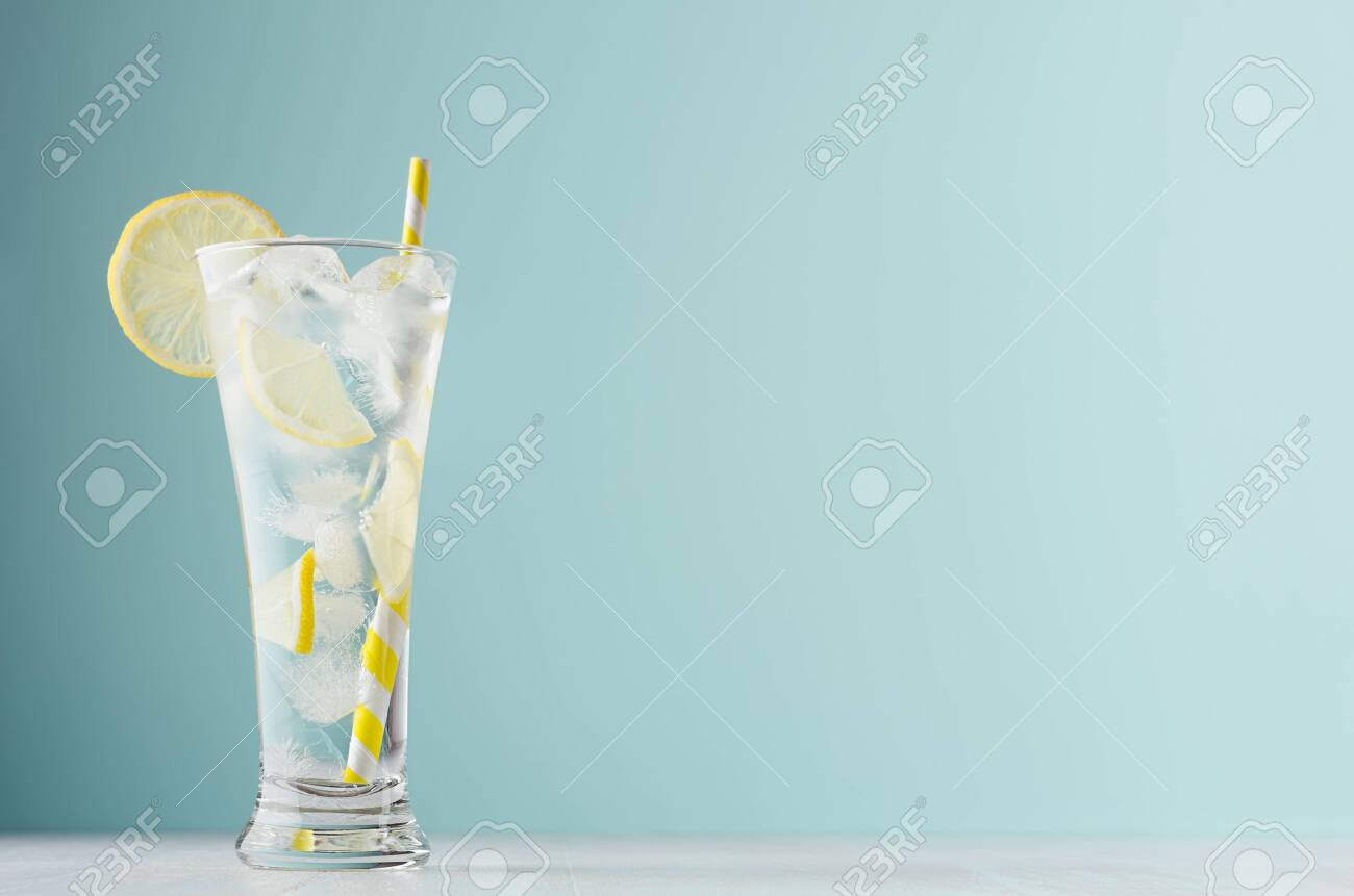Homemade diet transparent lemonade with lemon, ice cubes, soda, yellow striped straw in misted glass on white wood table, pastel green color background. - 129913005