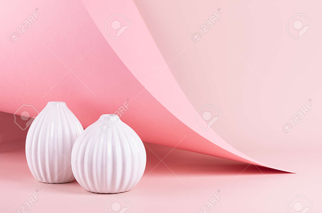 Delicate spring pink interior with ribbed white ceramic vases on soft light pastel background with hovering curved paper, peak. Fashion simple minimalist style. - 168468814
