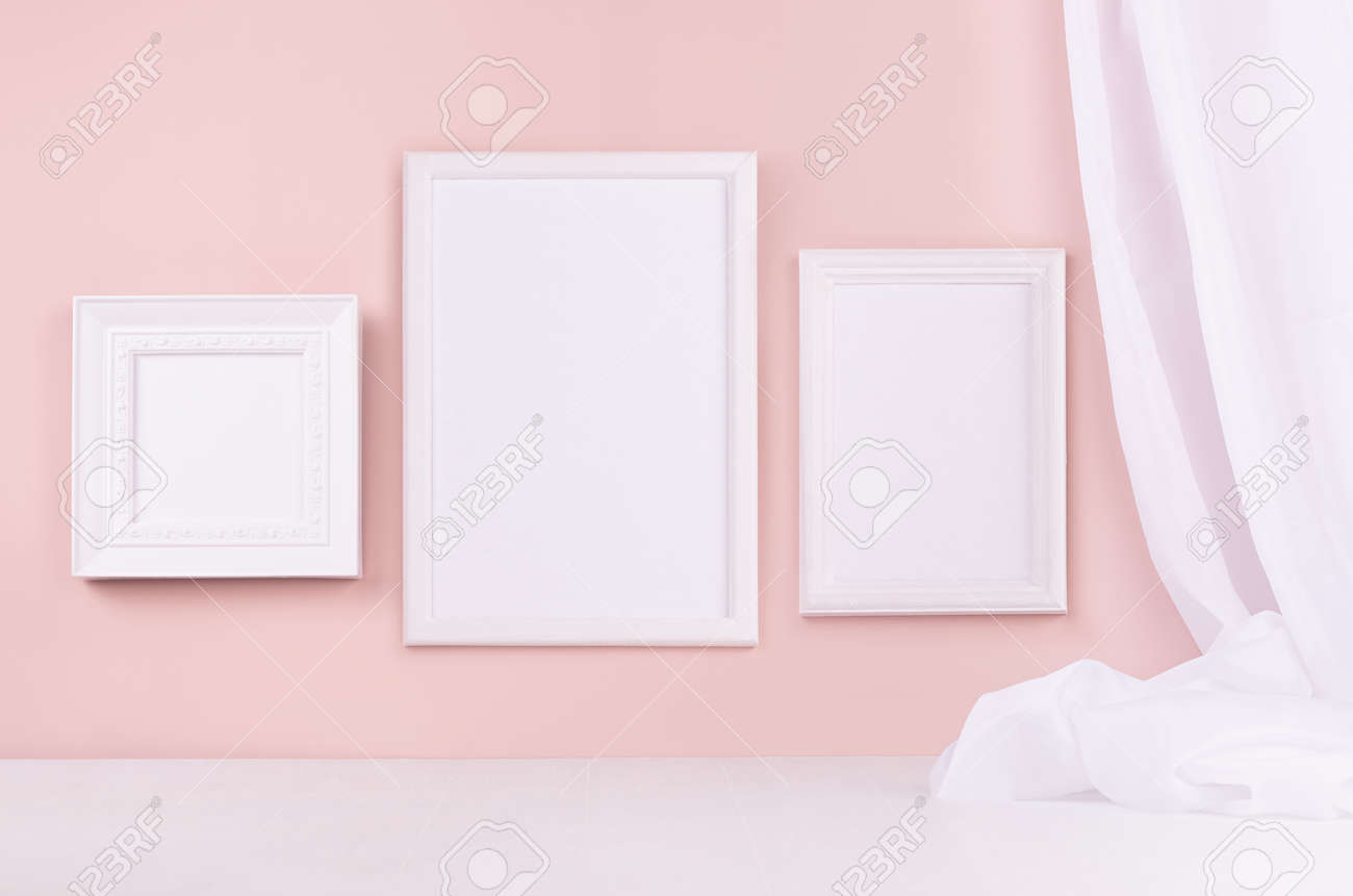 Minimal elegant gallery for display portfolio - three blank rectangle photo frames with flow silk curtain hanging on pink wall and white wood table. - 168468816