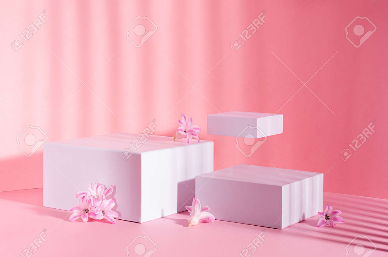 Fashion pastel pink mock up with set of white square podiums for presentation cosmetic, accessories and produce in sunlight with levitate spring hyacinth flowers. - 168468861