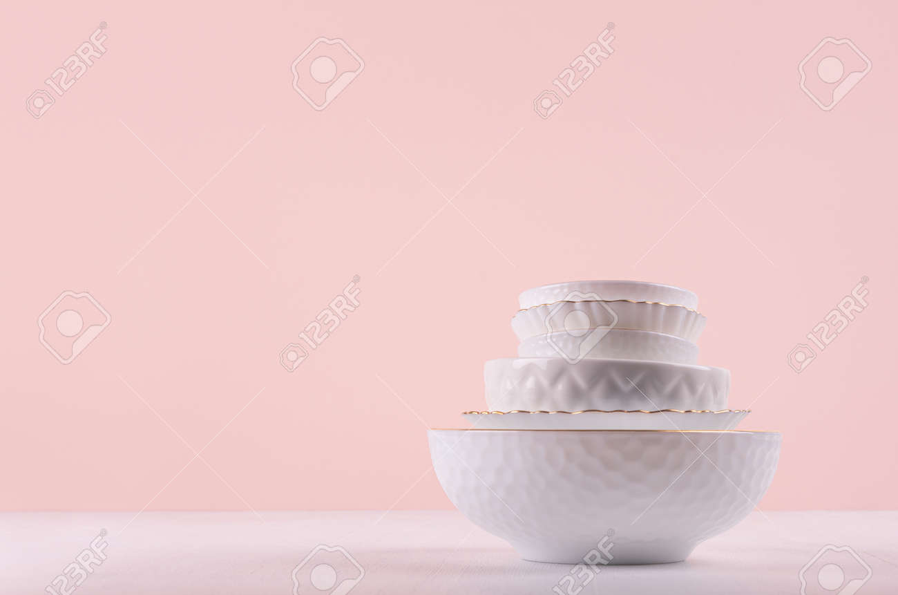 White ceramic dishes with thin gold border, different tracery form on white wood table in delicate pastel pink interior. - 168468866