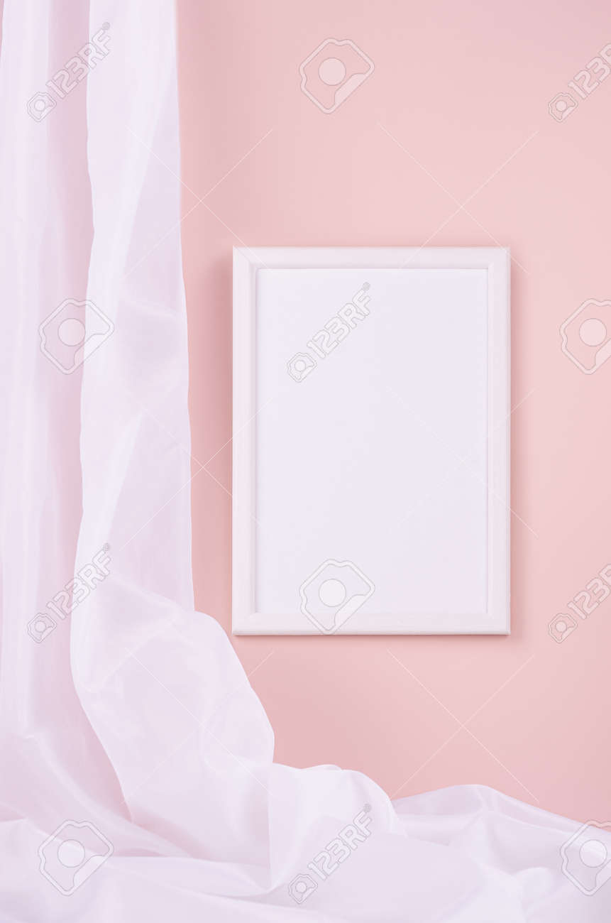 Delicate home decor with blank rectangle photo frame hanging on pastel pink wall, flow of silk curtain, vertical. Mock up for portfolio, design or text. - 168468876