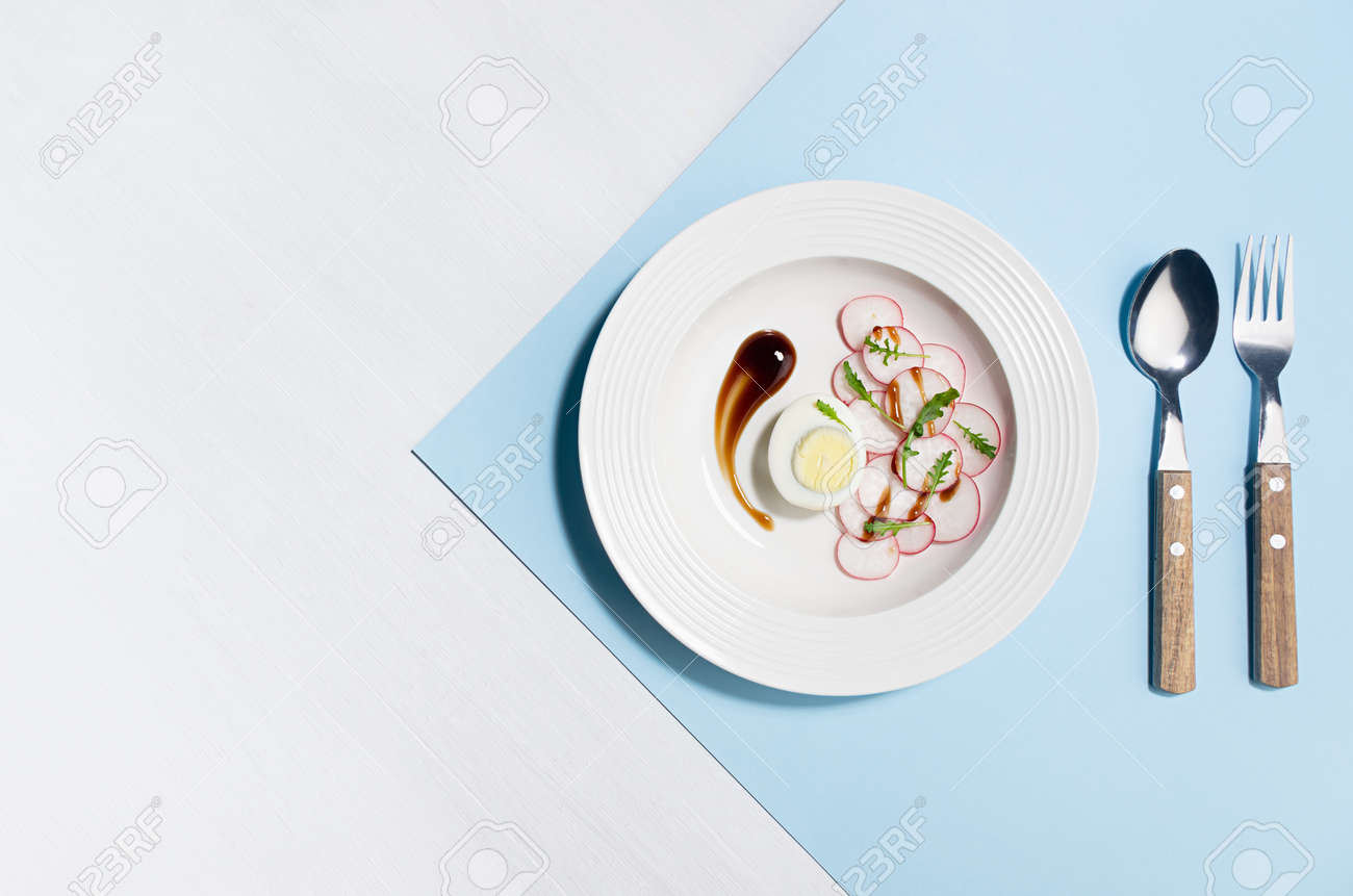 Fresh vegetarian salad of radish, arugula and eggs with cutlery, teriyaki sauce art plating on white wood table, blue color with shadow in sunlight, flat lay. Colorful modern geometric style food background. - 168468877