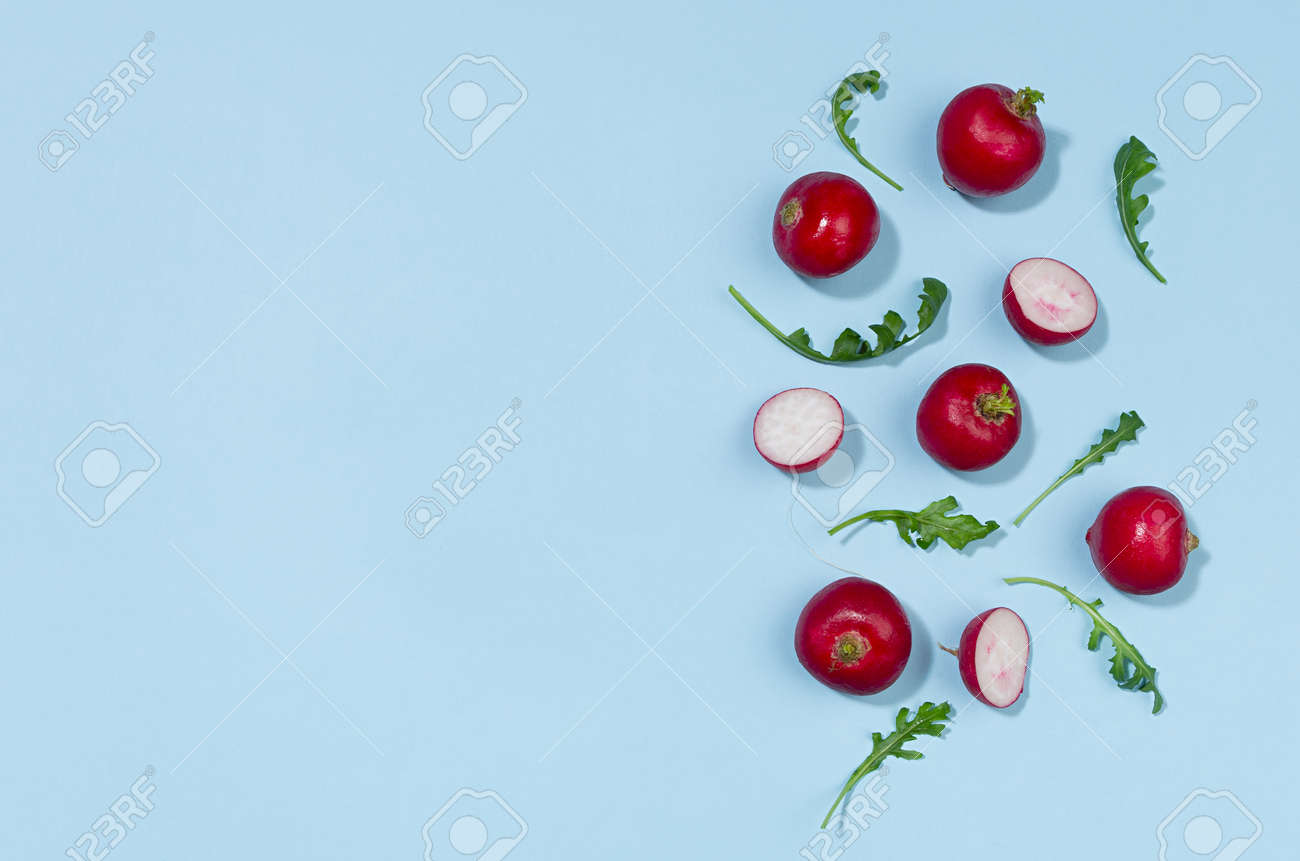Radish and arugula with shadow on blue background as border, top view, copy space. Colorful spring vegetable background. - 168468891