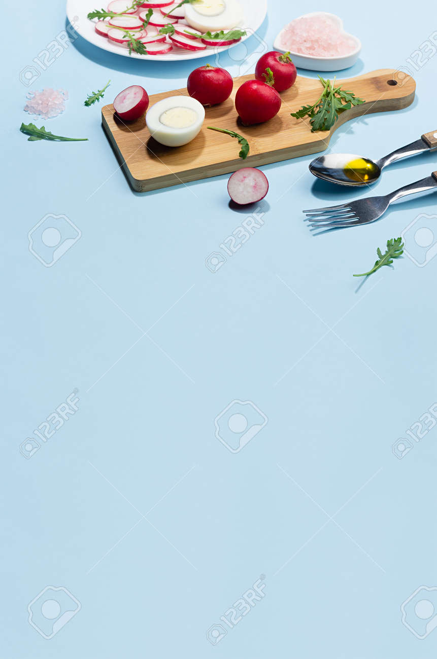 Dieting salad of fresh vegetables - radish, arugula and eggs with shadow in hard light on blue background and white wood table, border, vertical. - 168468895