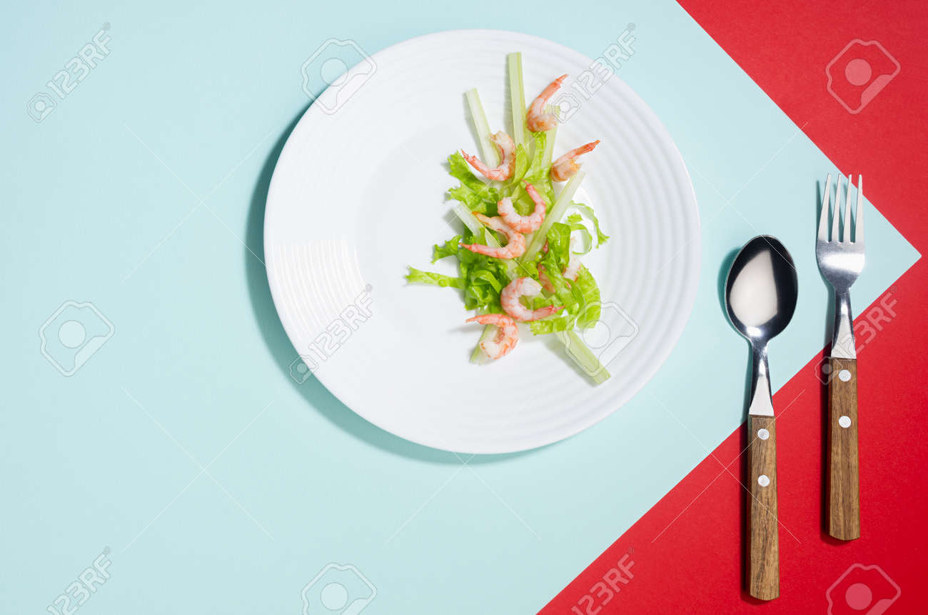 Modern elegant geometric style in food - appetizer of shrimps, greens, celery, teriyaki sauce in white plate with cutlery with shadow in sunlight on red and minty background, flat lay. - 168468904