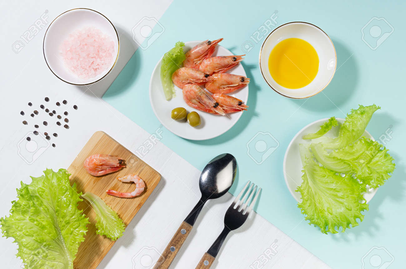 Healthy lifestyle - cooking of fresh salad of prawn, green salad, olive, black pepper, pink salt in sunlight with shadow, flat lay, on white wooden table, minty background. - 168468909