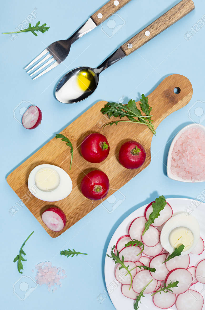 Spring fresh salad of radish, arugula and eggs, ingredients and cooking on blue background with shadow in sunlight. Colorful modern simple style of food. Top view, vertical. - 168468910