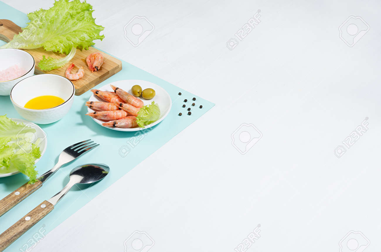 Recipe of organic salad of green salad, shrimps, spice and oil on minty background, copy space. Modern trend concept with shadow and hard light. - 168468914