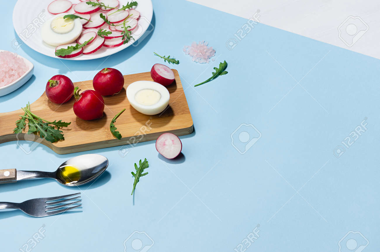 Dieting salad of fresh vegetables - radish, arugula and eggs with shadow in hard light on blue background and white wood table, border. - 168468915