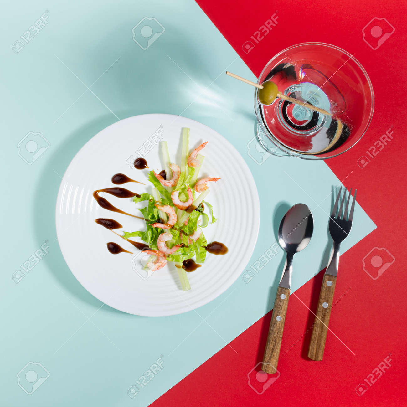 Spring seafood salat of shrimps, greens, celery, balsamic sauce with martini cocktail in white plate on red and minty color background with shadow in hard light, top view, square. - 168468916