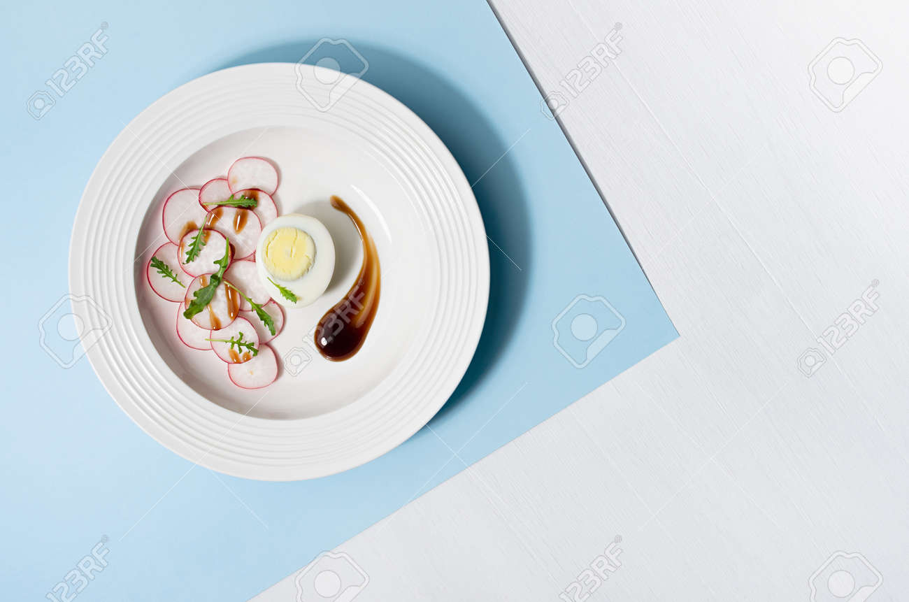Spring vegetable salad of radish, arugula and eggs with balsamic sauce in white plate on pastel blue background with shadow in hard light, top view. - 168468922