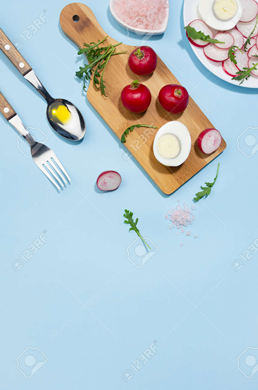 Healthy lifestyle - cooking of spring salad of raw fresh vegetables - radish, arugula with eggs in sunlight with shadow, top view, vertical, on white wooden table, blue background. - 168468924