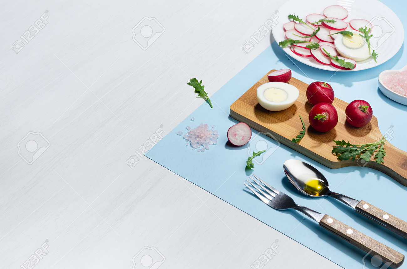 Recipe of organic salad of radish, arugula and eggs with olive oil on blue background, border, copy space. Modern concept with shadow and hard light. - 168468926