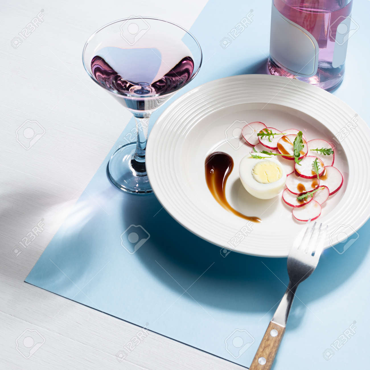 Fresh salad of radish, arugula and eggs with teriyaki sauce art plating, glass of rose wine, bottle, cutlery on white wood table, blue color with shadow in sunlight, square. Colorful geometric style food background. - 168468973