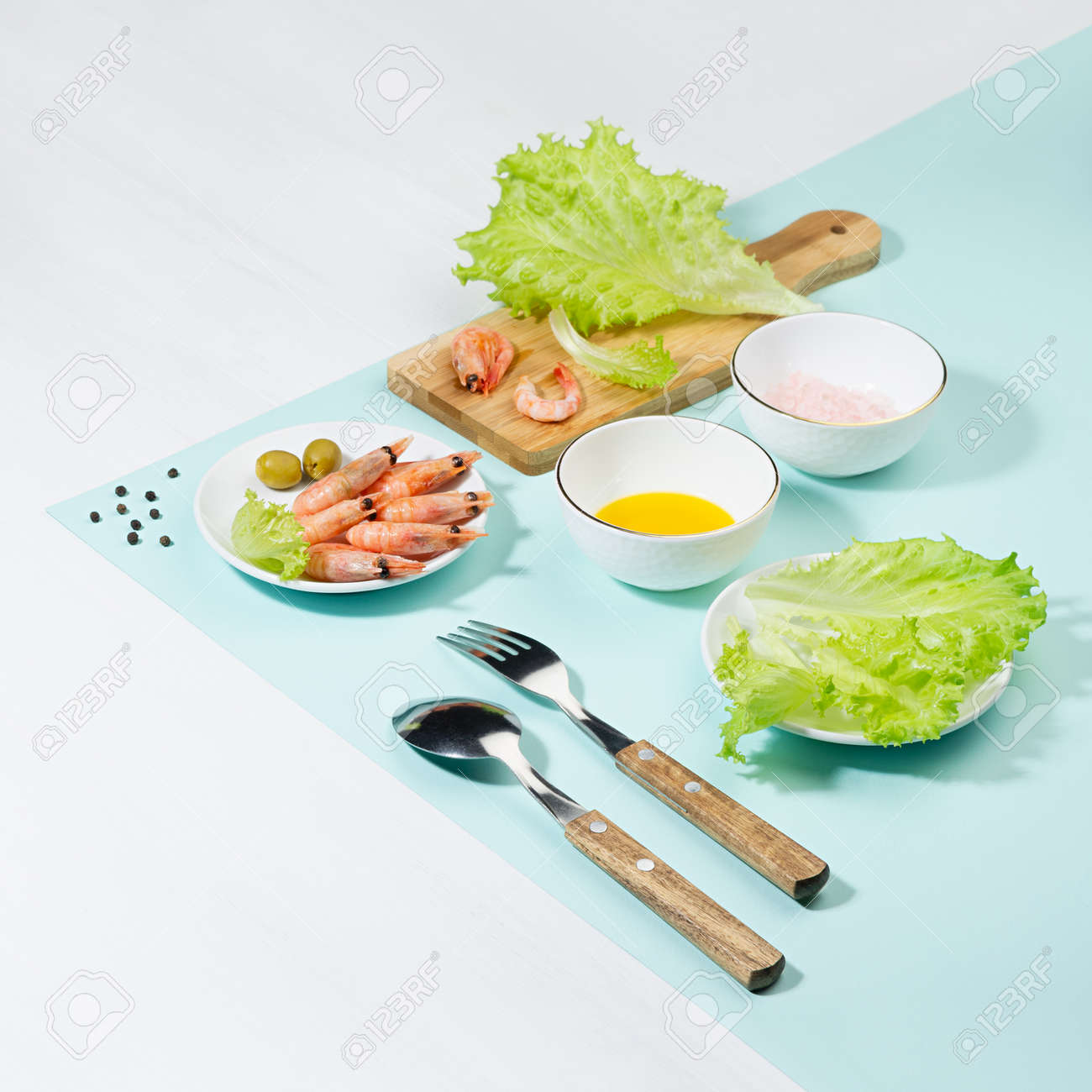 Dieting salad of fresh greens, shrimps with shadow in hard light on pastel mint color and white wood table, square. Summer healthy food in color modern style. - 168468974