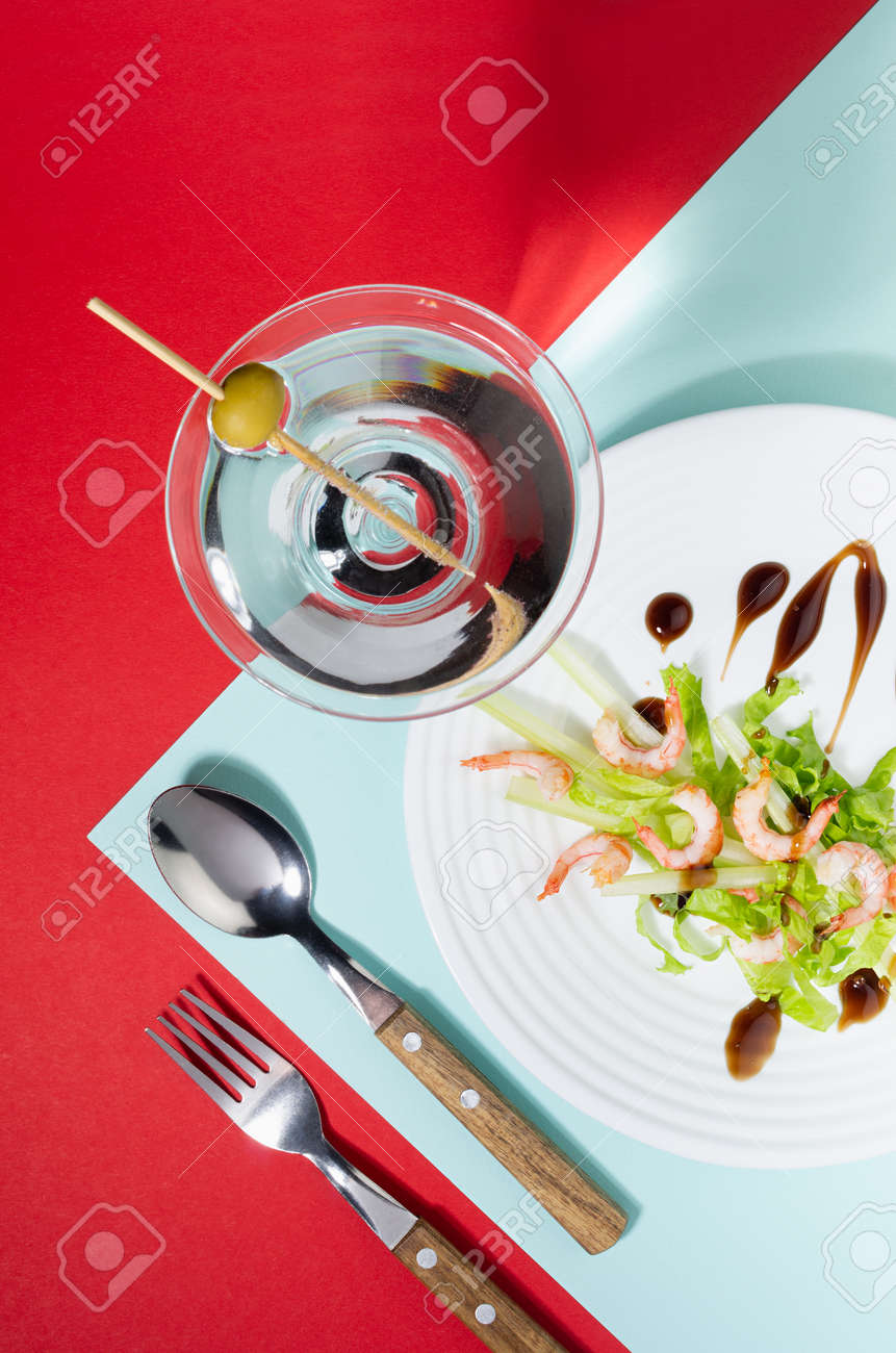 Elegant food in trend color style - green salad with shrimps and cocktail decorated green olive with shadow in hard light on red and minty background, top view, vertical. - 168468978