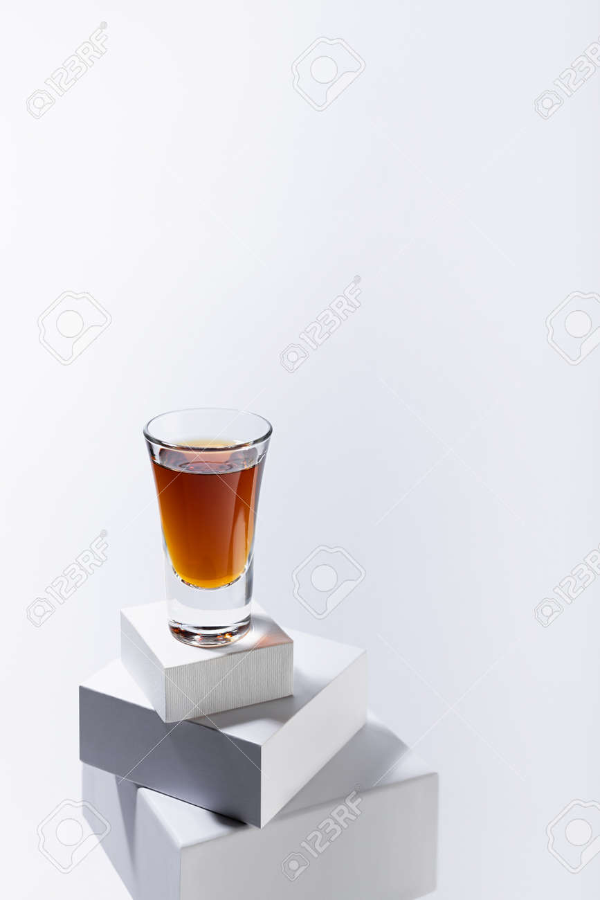 Brown old cognac in shot glass on stack of white boxes as podium in soft light white abstract space, luxury minimal geometric style, vertical. - 173589694