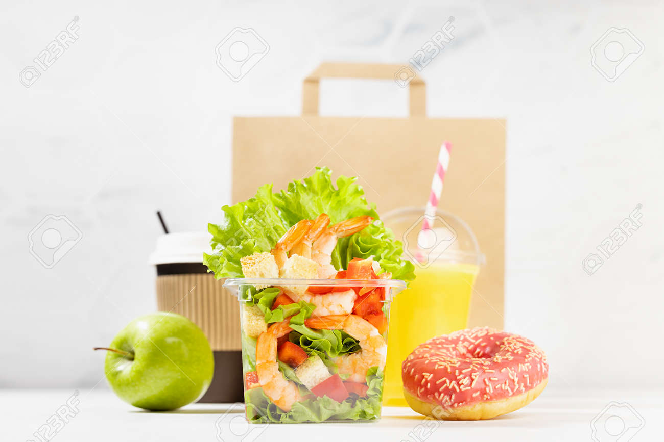 Healthy daily diet plan - set of orange juice, tropical salad with shrimps in plastic box, pink donut, packet in white interior. Advertising for restaurant take away, delivery food service. - 173589710