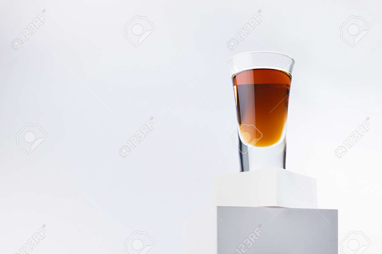 Bright brown brandy in glossy shot glass in sunlight with reflections on abstract white square podiums in soft light space, exquisite minimal style. - 173589292