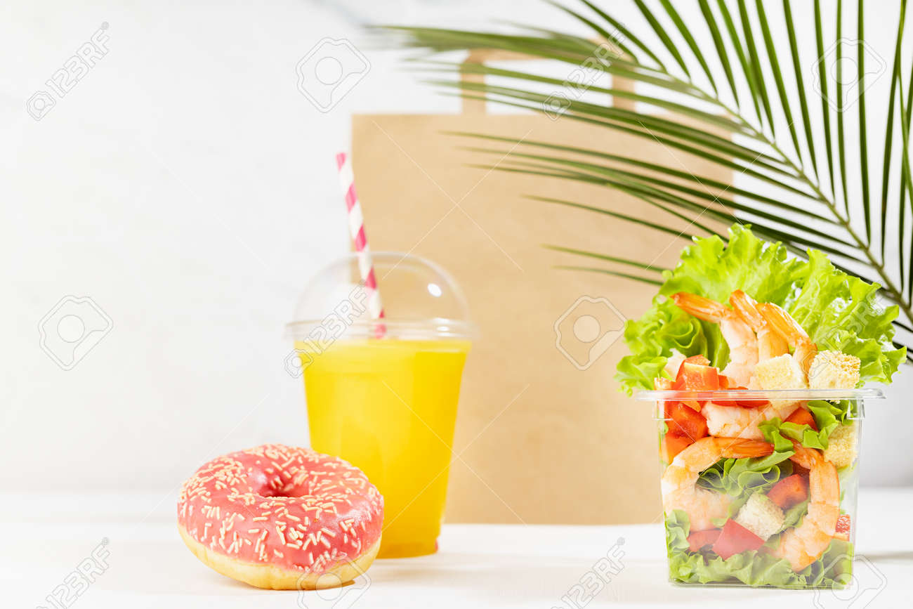 Healthy food set with fresh orange juice, tropical salad in plastic pack, pink donut, packet on in white interior with palm leaf. Concept advertising for restaurant take away or delivery food service. - 173589713