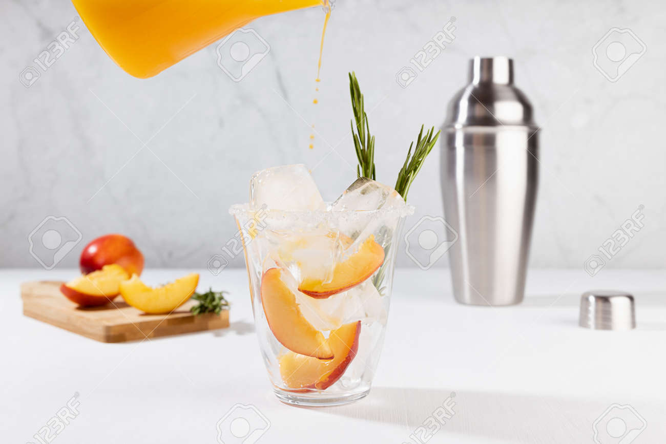 Cooking healthy summer peach juice - cocktail pour of jug in glass with ice, rosemary twig, sugar rim, ingredients in elegant white interior on soft light wood table. - 173589451