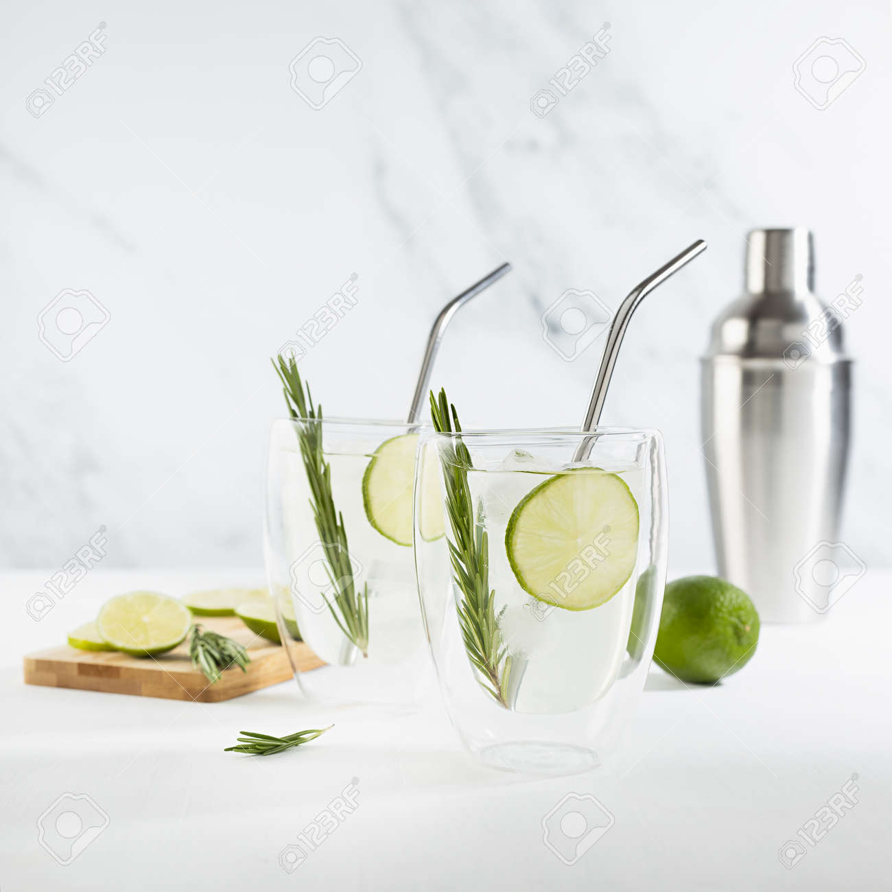Organic mojito cocktail cooking with citrus fruit slices, ice cubes, green rosemary twig, ingredients, silver shaker, straws, cut board in two transparent mugs on white wood table, marble wall. - 173589720