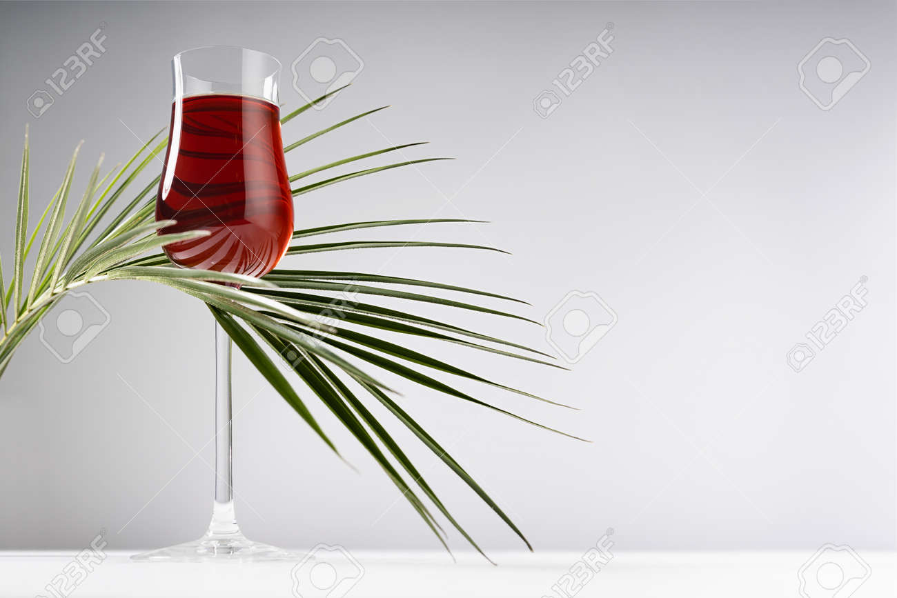 Red porto in luxury high glass decorated elegant curved green palm leaves in hard light with shadow in soft light white abstract interior wooden table, gray wall. - 173589727