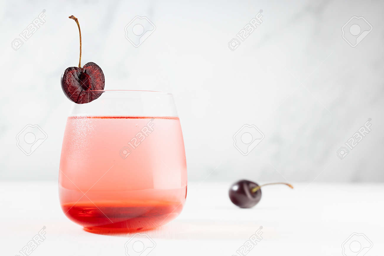 Summer refreshing cold healthy lemonade with cherry syrup, fruit slice in misted glass modern white restaurant interior with marble wall. - 173589734