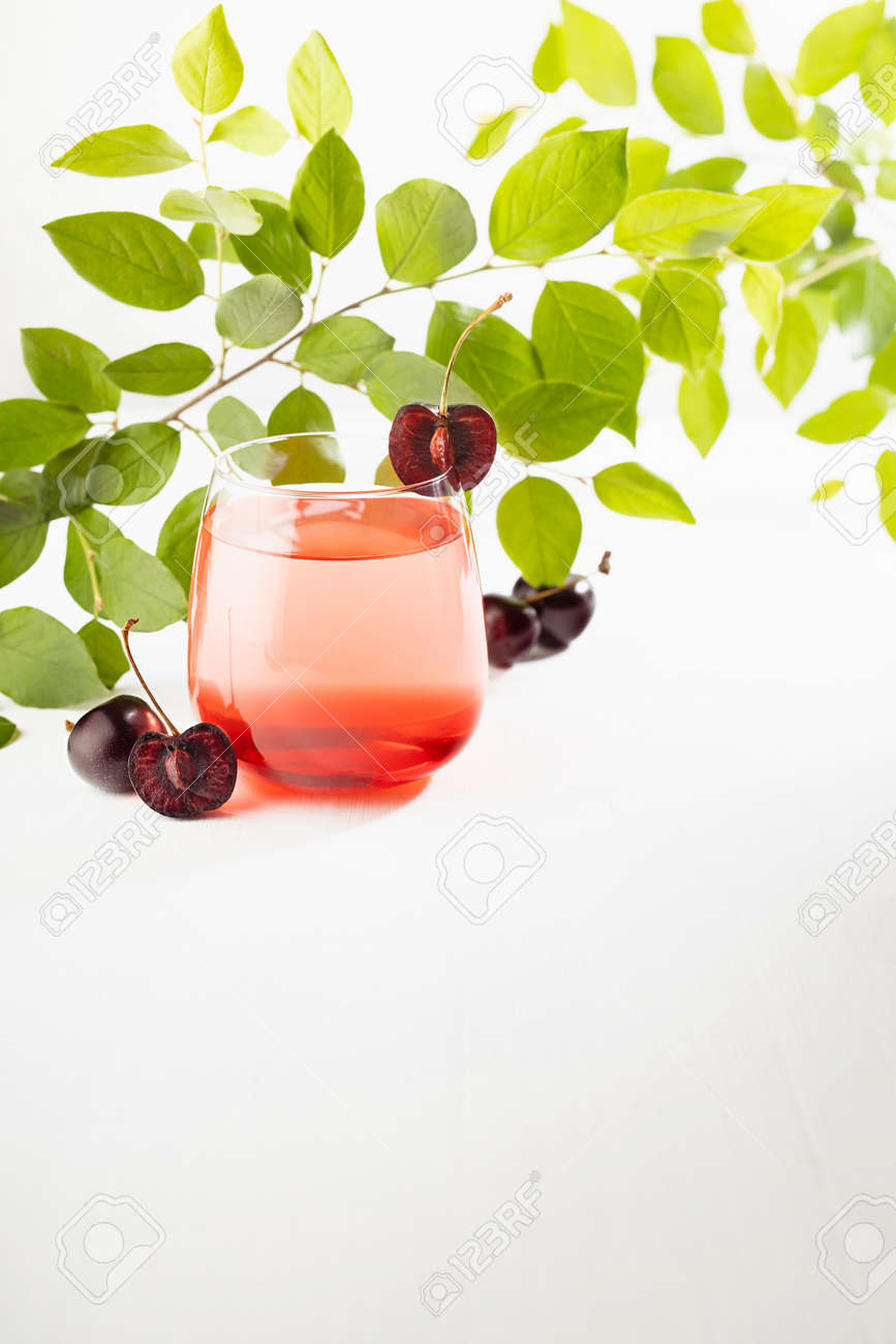 Bright sunny summer cherry cocktail with slice cherry, green leaves in gold sunlight on white wood table in soft light white bar interior or garden, vertical. - 173589765