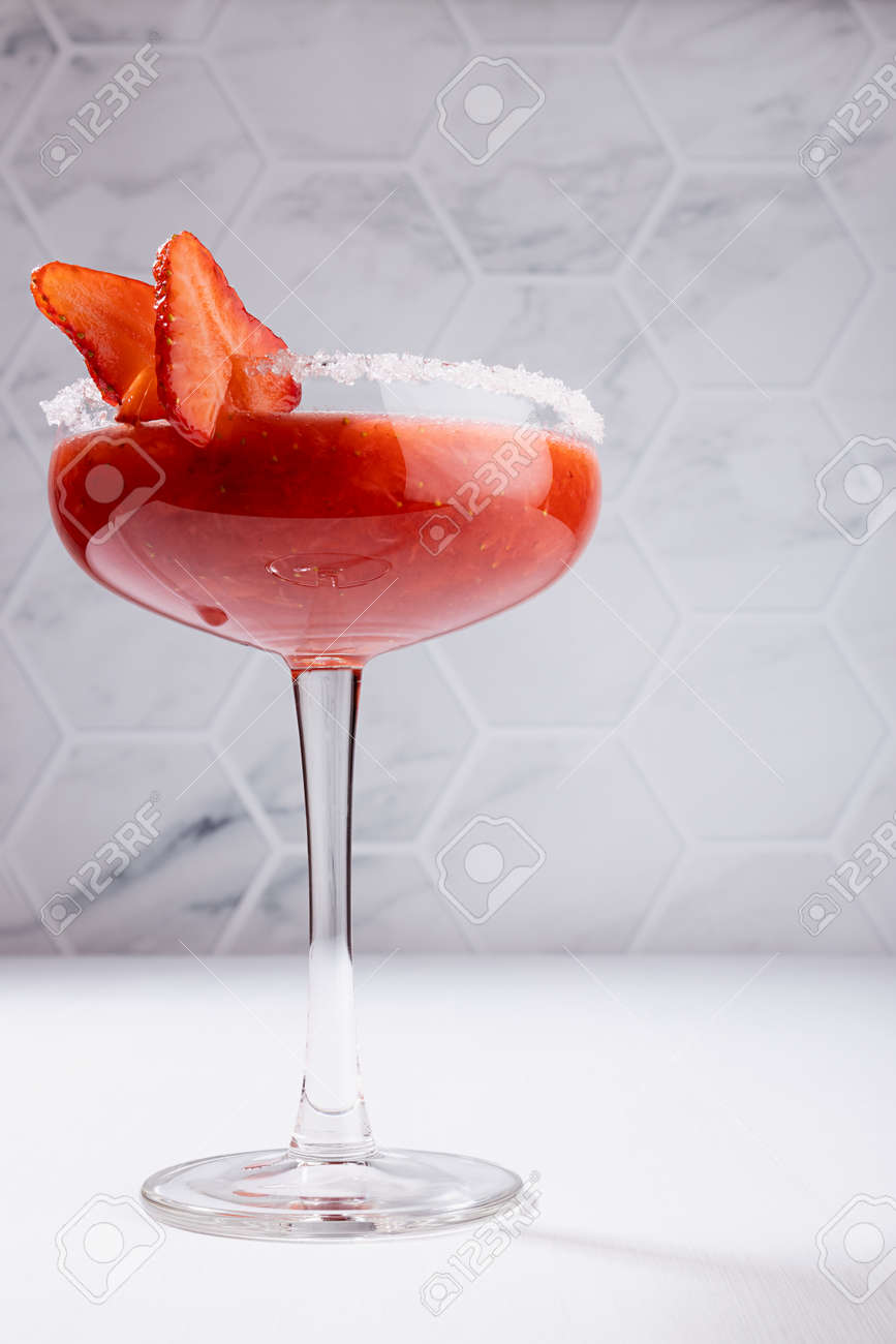 Tropical fresh strawberry juice with pulp in high glass goblet decorated sugar rim, fruit slice in modern white restaurant interior, vertical. - 173589429