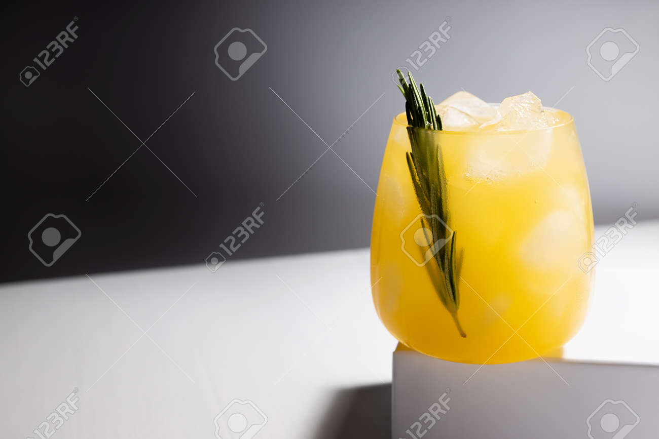 Fresh misted orange alcohol cocktail in glass with ice, green rosemary twig on podium in sunlight with shadows in elegant minimal black and white interior. - 173589771