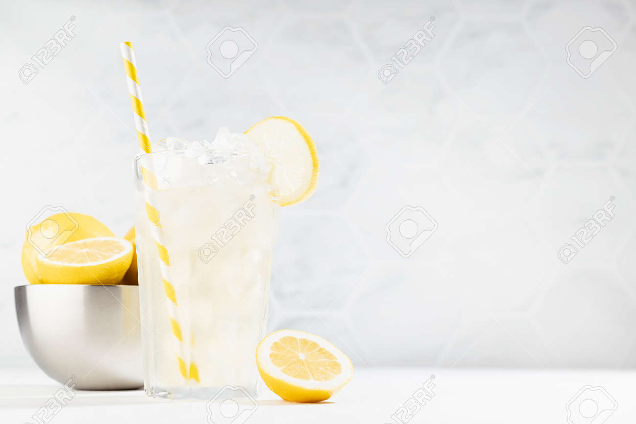 Cold juicy lemon cocktail in glass with straw, ice cubes, yellow lemons in silver bowl in summer sunlight in soft light white kitchen interior with marble tile. - 173589604