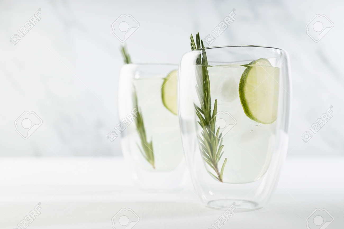 Healthy summer vitamin cold tonic drink with lime juice, ice, green rosemary twig in two glass mugs on white wood table and soft light marble wall. - 173589774