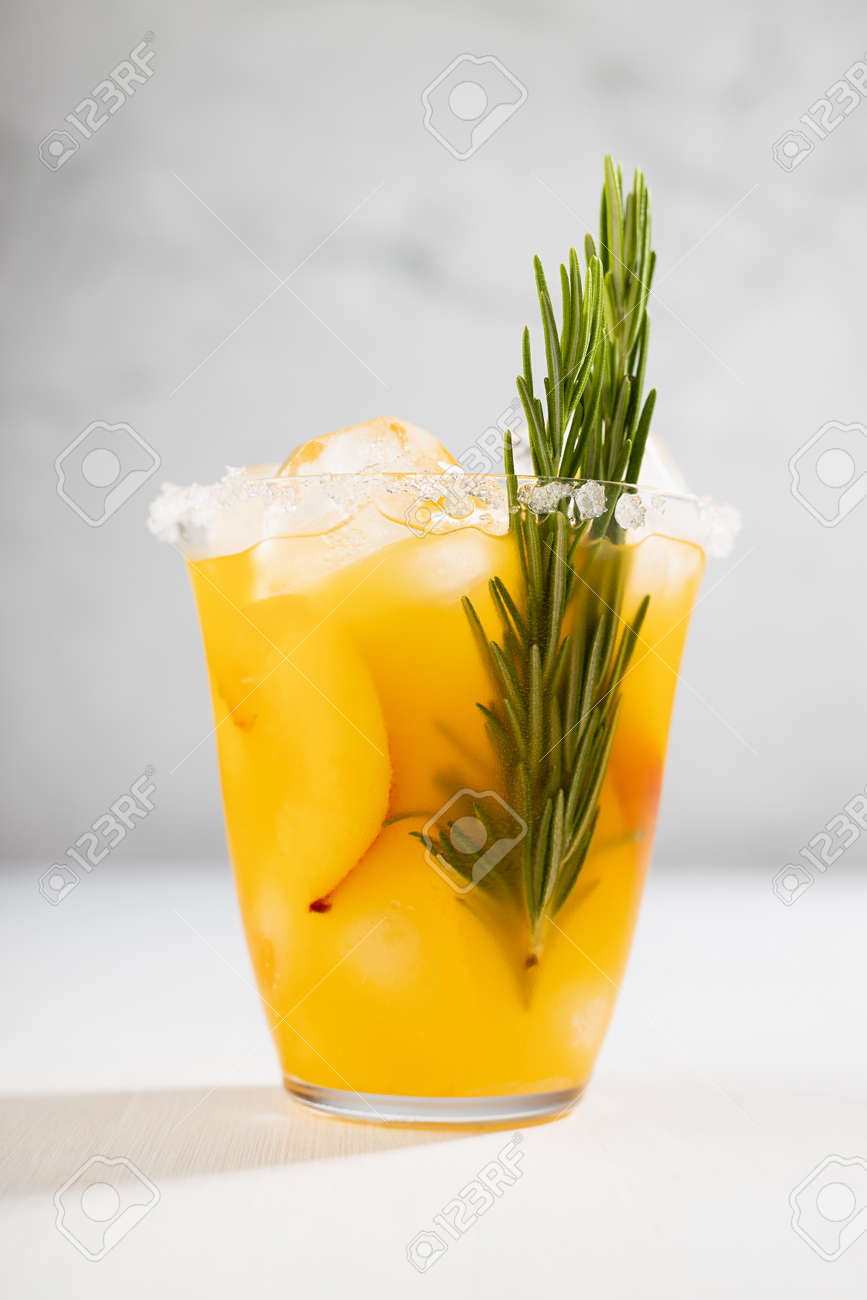 Fresh cold peach drink in glass with ice cubes, green rosemary, fruit slice, sugar rim in soft light white kitchen interior, vertical. - 173589420