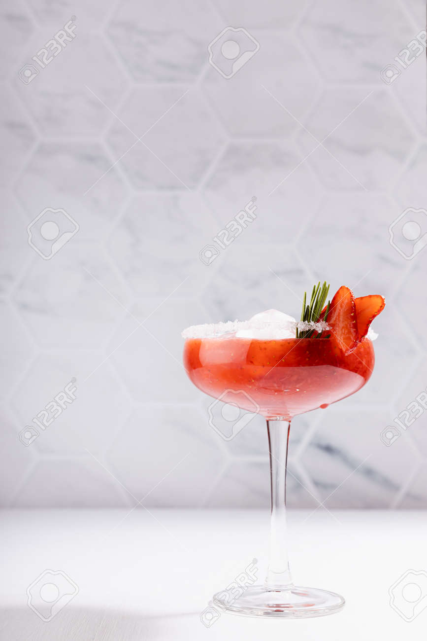 Fresh classic strawberry margarita cocktail with green rosemary twig, ice cube, fruit slices, sugar rim in modern white kitchen interior on wooden table in sunlight, vertical. - 173589776