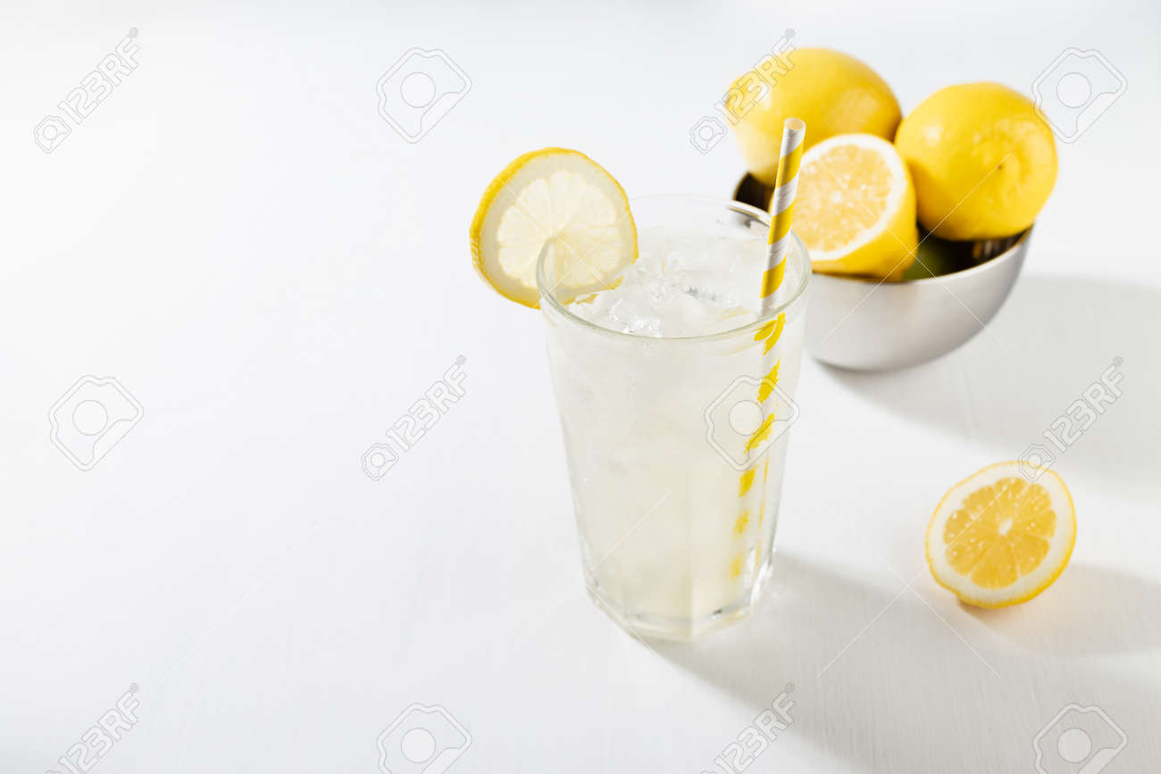 Fresh summer classic lemonade in glass with straw, ice, ingredients - lemons in silver bowl in soft light modern white kitchen interior with marble tile, sunlight. - 173589235