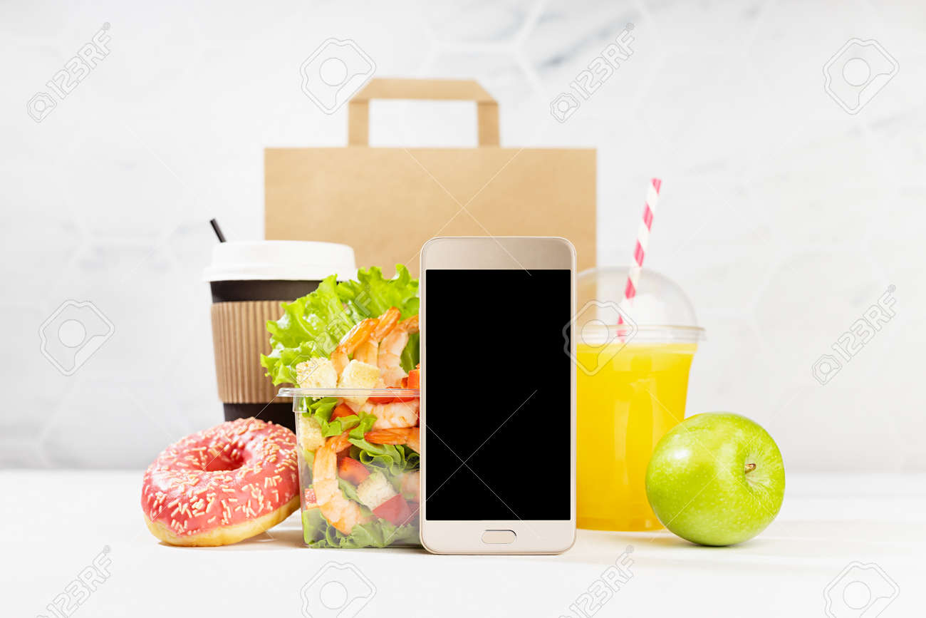 Lunch food set with coffee cup, orange juice, shrimp salad in plastic pack, apple, donut, packet, fruit, blank phone in white interior. Advertising for restaurant take away or delivery food service. - 173913742