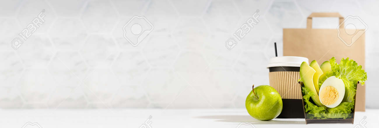 Wellness food banner - set of salad with lettuce, avocado, egg, cup of coffee, green apple, paper pack in light white interior. Concept advertising for restaurant take away or delivery food service. - 173913836