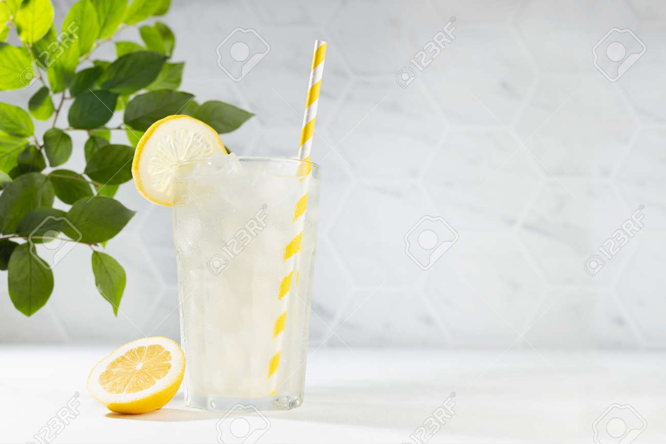 Cold juicy lemon cocktail in glass with straw, ice cubes, yellow slice with green branch in summer sunlight in soft light white kitchen interior with marble tile or garden. - 173914010