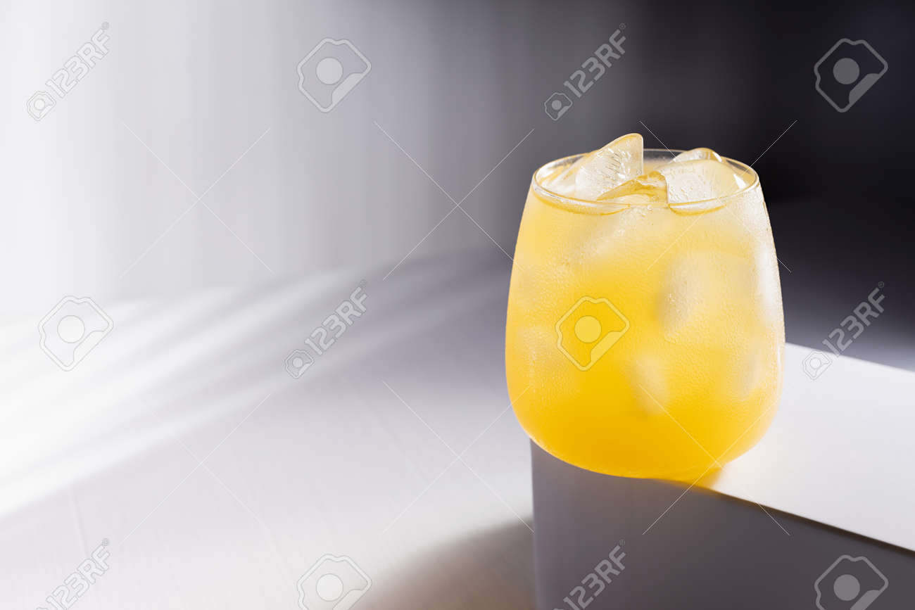 Cold orange fruit drink in glass on podium in elegant minimsl dark white wnd gray abstract interior with hard light and striped shadows. - 173913760