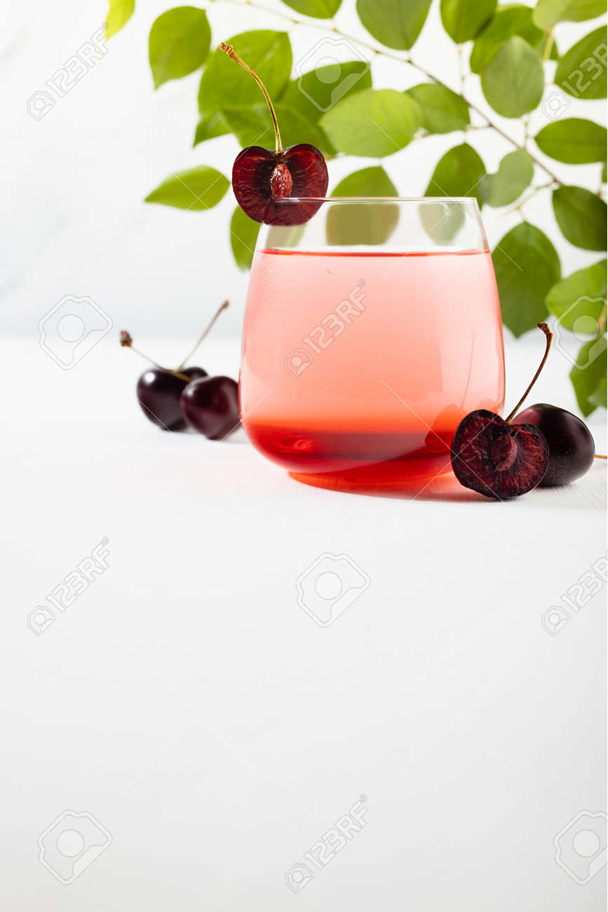 Cold cherry layered cocktail in misted glass with slice cherries, green fresh leaves in sunlight on soft light white wood table, marble wall, vertical. - 173913638