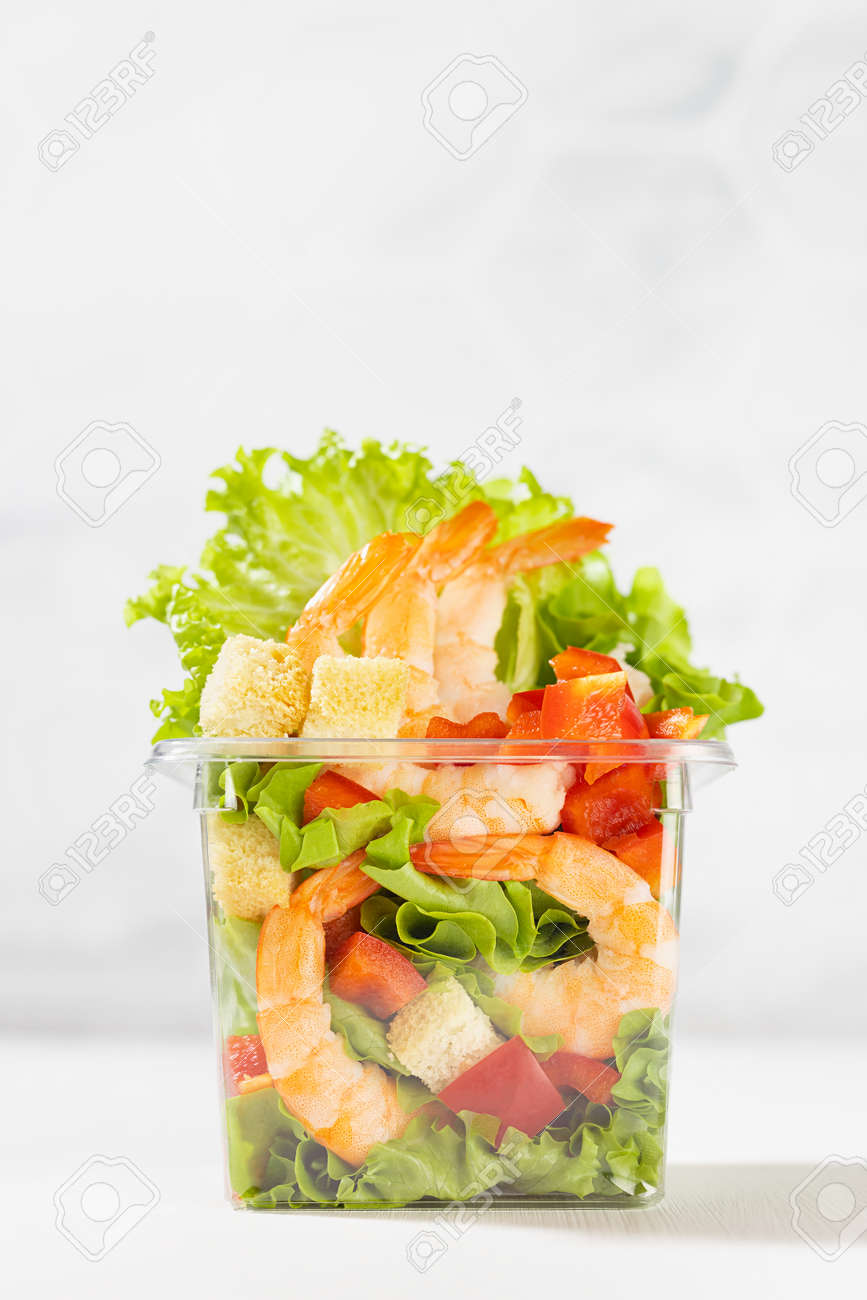 Organic vitamin meal - fresh sea food salad with shrimps, lettuce, red bell pepper, croutons in plastic box in white restaurant interior with marble tile wall, vertical. - 173913591