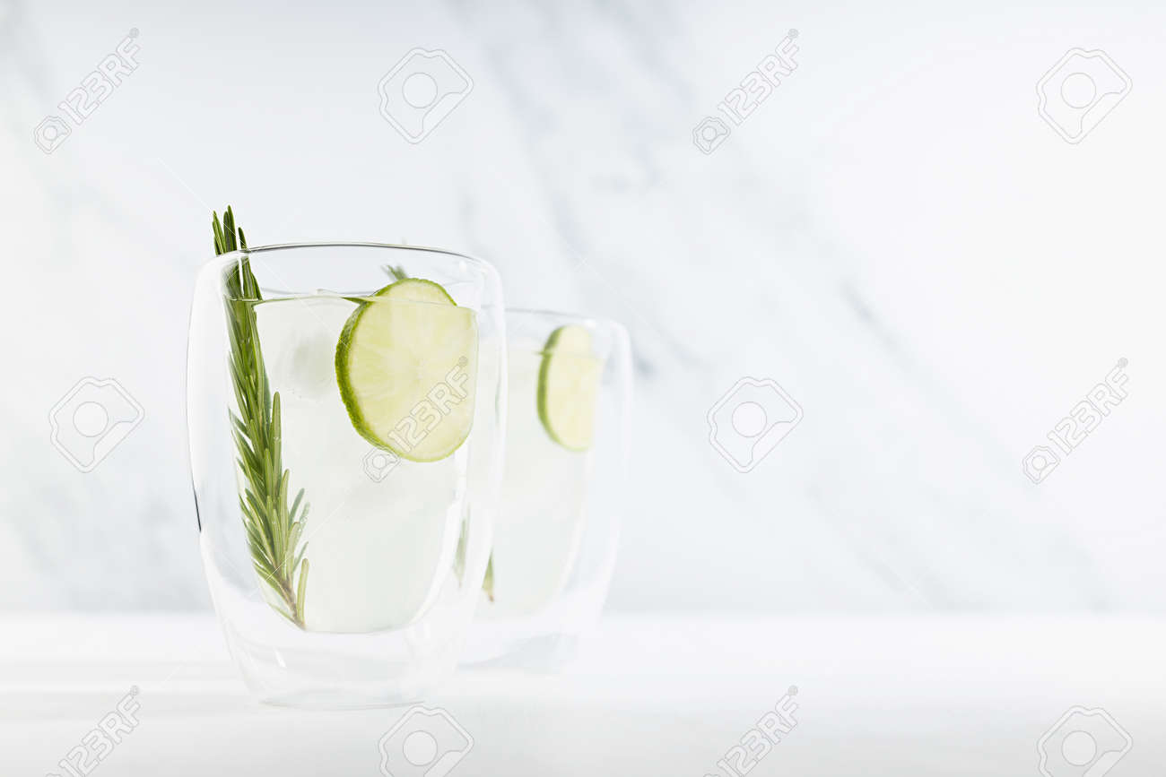 Fresh citrus infused homemade lemonade with ice cubes, lime slices, green rosemary twig in two mugs in soft light white kitchen interior in sunny day. - 173913734