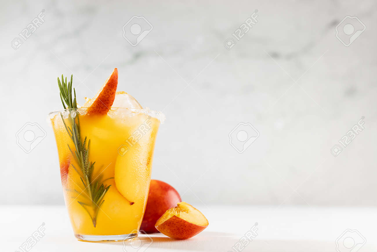 Healthy summer juice - peach cocktail with ice, rosemary twig, sugar rim, fruit slices in misted glass and ingredients in elegant white interior on soft light wood table. - 173913707