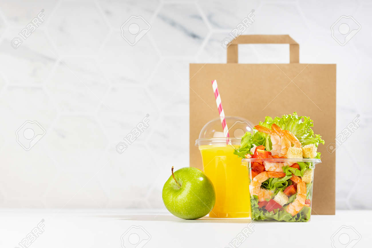 Healthy food set with fresh orange juice, tropical salad with shrimps, vegetables, apple in plastic packaging, packet in white interior. Concept advertising for restaurant take away, delivery service. - 173913874