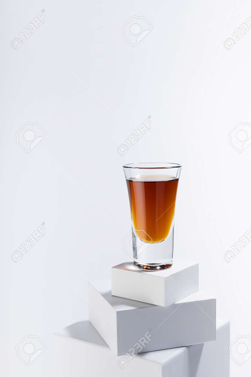 Golden scotch in shot glass in sunlight with shadows on white square podium with reflections in soft light abstract space in minimal modern style, vertical. - 173913658