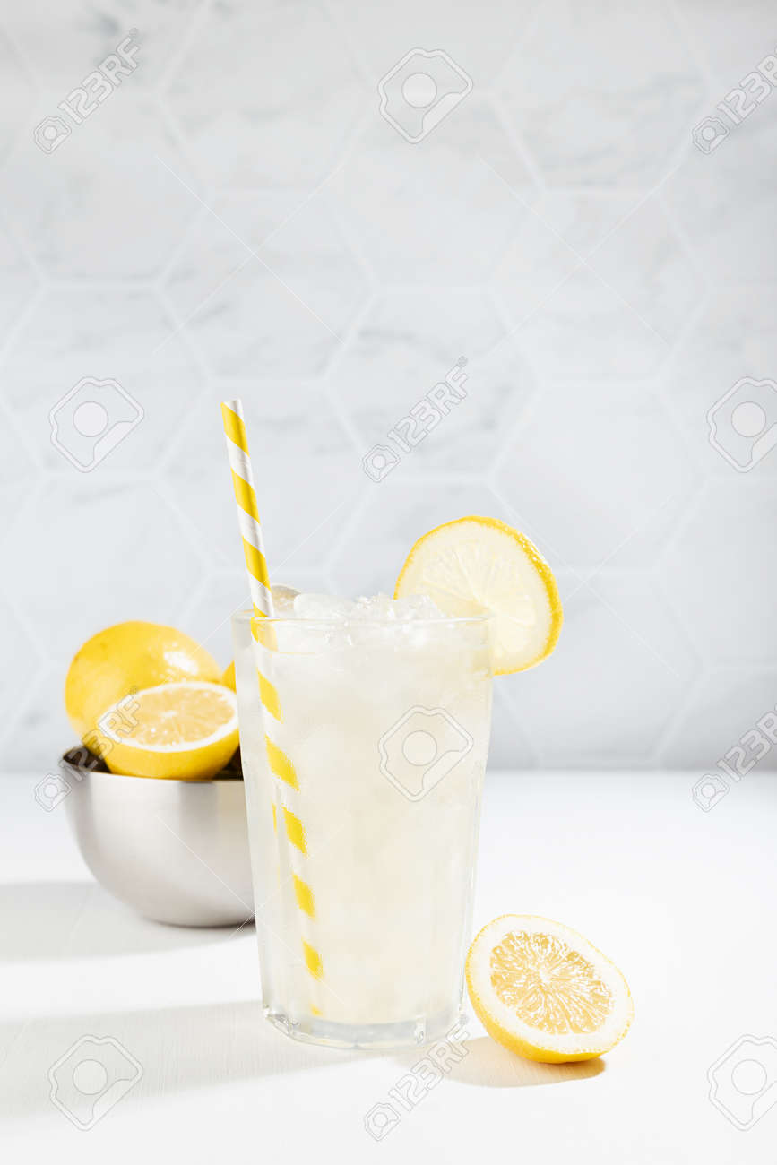 Homemade traditional refreshing cold sour lemonade infused beverage with ice, straw in glass with yellow lemon slice, silver crockery in modern white kitchen interior in sun beam, vertical. - 173913692