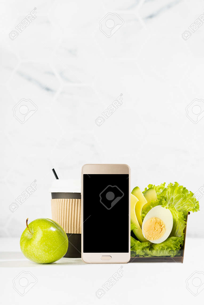 Organic cuisine - blank phone with set of green salad with lettuce, avocado, egg, cup of coffee, apple in white interior. Mockup advertising for delivery service, take away restaurant, online order. - 173913712